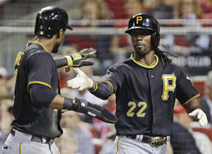 Photo - Pittsburgh Pirates' Andrew McCutchen (22) and Starling Marte slap hands with each other after they scored on a hit by Marlon Byrd off Cincinnati Reds starting pitcher Homer Bailey during the third inning of a baseball game, Friday, Sept. 27, 2013, in Cincinnati. (AP Photo/Al Behrman)