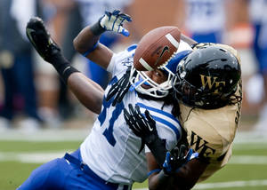 Photo -   Duke's Tony Foster, left, breaks up a pass intended for Wake Forest's Sherman Ragland III, right, during the second half of an NCAA college football game in Winston-Salem Saturday, Sept. 29, 2012. Duke defeated Wake Forest 34-27. (AP Photo/Winston-Salem Journal, Lauren Carroll)
