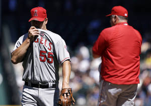 Photo - Los Angeles Angels starting pitcher Joe Blanton, left, heads off the field after being relieved in the fifth inning of a baseball game against the Seattle Mariners, Sunday, July 14, 2013, in Seattle. (AP Photo/Elaine Thompson)
