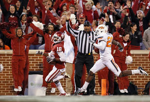 photo - BEDLAM FOOTBALL: Oklahoma's Jalen Saunders (18) returns a punt for a touchdown past Oklahoma State's Larry Stevens (20) in the fourth quarter during the Bedlam college football game between the University of Oklahoma Sooners (OU) and the Oklahoma State University Cowboys (OSU) at Gaylord Family-Oklahoma Memorial Stadium in Norman, Okla., Saturday, Nov. 24, 2012. OU won, 51-48 in overtime. Photo by Nate Billings , The Oklahoman