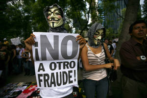"Photo -   Wearng a Guy Fawkes mask, a Mexican unhappy with the presidential election results, holds a banner that reads in Spanish; ""No to another fraud!,"" during a march in Mexico City, Saturday, July 7, 2012. The protestors are marching in rejection of the final count in the presidential election showing former ruling party candidate Enrique Pena Nieto as the victor. They believe the PRI engaged in vote-buying that illegally tilted millions of votes. PRI officials deny the charge. (AP Photo/Marco Ugarte)"