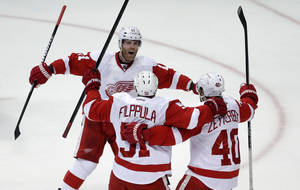Photo - Detroit Red Wings center Valtteri Filppula, center celebrates his goal with right wing Daniel Cleary, left, and center Henrik Zetterberg during the second period in Game 7 of their first-round NHL hockey Stanley Cup playoff series against the Anaheim Ducks in Anaheim, Calif., Sunday, May 12, 2013. (AP Photo/Chris Carlson)