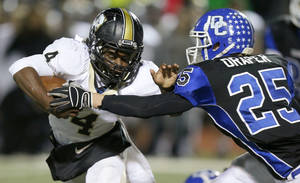 McAlester's Jarome Smith, left, fights off Deer Creek's Chad Draper during a 2012 playoff game.   Photo by Bryan Terry, The Oklahoman Archives