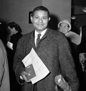 Photo - FILE - In a Feb. 25, 1957 file photo, William Worthy, Afro-American correspondent for the Baltimore Weekly, at the U.S. Passport Agency in New York. Worthy, a foreign correspondent who defied travel bans to Cold War adversaries of the United States, died May 4 in Brewster, Mass., according to the The Nieman Foundation for Journalism at Harvard University. He was 92.  (AP Photo/Jacob Harris, File)