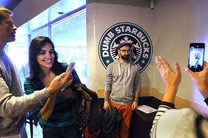 Photo - LOS ANGELES-CA-FEBRUARY 9, 2014: Jeffrey Eyster, Kimmie Fadem, Alexander Walter, and Kaori Walter, from left, take photographs while waiting in line inside a coffee shop mocking Starbucks called Dumb Starbucks in Los Feliz for complimentary drinks on February 9, 2014. (Christina House / For The Times)