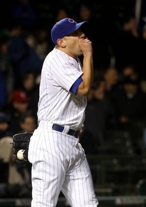 Photo - Chicago Cubs relief pitcher Shawn Camp reacts after giving up a two-run home run to Texas Rangers' Adrian Beltre, also scoring Elvis Andrus, during the eighth inning of a interleague baseball game, Tuesday, April 16 2013, in Chicago. (AP Photo/Charles Rex Arbogast)