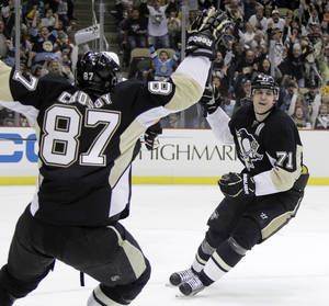 Photo -   Pittsburgh Penguins' Evgeni Malkin (71) celebrates his 50th goal of the season with teammate Sidney Crosby in the second period of an NHL hockey game against the Philadelphia Flyers in Pittsburgh Saturday, April 7, 2012. (AP Photo/Gene J. Puskar)