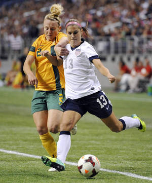 Photo - FILE - In this Oct. 20, 2013 file photo, USA forward Alex Morgan, right, tangles with Australia defender Teigen Allen during the first half of an international friendly women's soccer match in San Antonio. Portland's NWSL team is struggling without its star forward as she rehabs from a left ankle injury she sustained while training with the U.S. national team last fall. Morgan is oh-so-close close to her return.(AP Photo/Darren Abate, File)