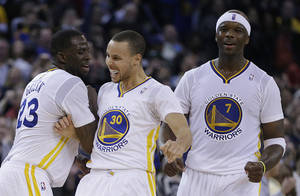 Photo - From left, Golden State Warriors' Draymond Green, Stephen Curry and Jermaine O'Neal celebrate during a timeout during the second half of an NBA basketball game against the Brooklyn Nets Saturday, Feb. 22, 2014, in Oakland, Calif. (AP Photo/Ben Margot)
