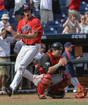 Photo - Mississippi's Aaron Greenwood, who scored the winning run against Texas Tech on a single by John Gatlin, celebrates left, as Texas Tech catcher Hunter Redman (5) crouches dejected, following an NCAA baseball College World Series elimination game in Omaha, Neb., Tuesday, June 17, 2014. (AP Photo/Ted Kirk)