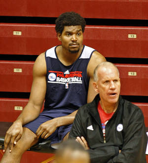 Photo -   Andrew Bynum, left and head coach Doug Collins watch practice during NBA basketball training camp, Tuesday, Oct. 2, 2012 in Philadelphia. (AP Photo H. Rumph Jr)