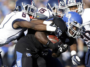 Photo - Buffalo running back Branden Oliver, front right, is tackled by Connecticut cornerback Jhavon Williams (6) and safety Ty-Meer Brown (15) during the first half of an NCAA college football game on Saturday, Sept. 28, 2013, in Buffalo, N.Y. (AP Photo/Mike Groll)