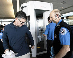 Photo - Airline passenger Danny Sadler, of Tulsa, has his back pocket checked by transportation security officer Jim Plank after he passes through a whole-body imaging machine at Tulsa International Airport. Work begins next week to install the technology at Will Rogers World Airport. Photo by Cory Young, TULSA WORLD ARCHIVES
