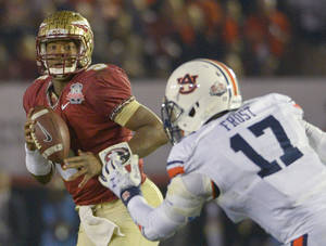Photo - Florida State's Jameis Winston looks to pass with Auburn's Kris Frost defending during the second half of the NCAA BCS National Championship college football game Monday, Jan. 6, 2014, in Pasadena, Calif. (AP Photo/Mark J. Terrill)