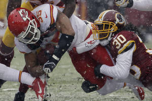 Photo - Kansas City Chiefs defensive back Quintin Demps (35) is stopped by Washington Redskins free safety E.J. Biggers (30) during the first half of an NFL football game in Landover, Md., Sunday, Dec. 8, 2013. (AP Photo/Pablo Martinez Monsivais)