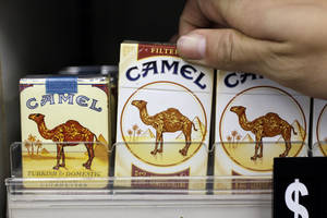Photo - In this Feb. 1, 2011 photo, Reynolds American Camel cigarettes appear on display with the new logo shown in center and right and older logo shown at left, at a liquor store in Palo Alto, Calif. Reynolds American Inc. reports earnings, Tuesday, Feb. 12, 2013. (AP Photo/Paul Sakuma)