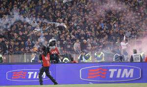 Photo - Napoli fans throw flares prior to the start of Italian Cup final match between Fiorentina and Napoli in Rome's Olympic stadium Saturday, May 3, 2014. At least one fan and one police officer were reportedly shot before the Italian Cup final between Napoli and Fiorentina, and the fan was in serious condition. As a result, the start of the final was delayed, and there were scenes of violence inside the stadium with a firefighter injured by fireworks thrown from the stands. The shootings occurred in an area where Napoli fans were gathering for the match, the ANSA news agency reported. (AP Photo/Gregorio Borgia)