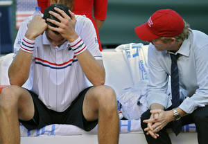 photo -   John Isner of US, left, laments beside his sport manager, Jim Courier, right, after he lost the second single match at Davis Cup World Group Semi-final tennis match against Nicolas Almagro, in Gijon, northern Spain, Friday, Sept. 14 , 2012. Almagro won the match 6-4, 4-6, 6-4, 3-6, 7-5. (AP Photo/Alvaro Barrientos)