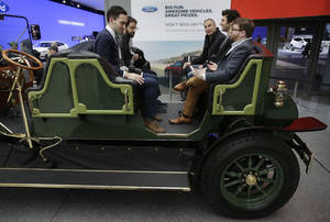 Photo - Visitors to the New York International Auto Show sit in an electric carriage prototype in New York, Thursday, April 17, 2014.  A prototype of the old-timey electric cars that Mayor Bill de Blasio would like to take the place of horse-drawn carriages on New York City streets will be unveiled at the New York Auto Show on Thursday. (AP Photo/Seth Wenig)
