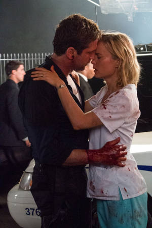 "Photo - Gerard Butler, left, and Radha Mitchell in a scene from ""Olympus Has Fallen.""  FILMDISTRICT PHOTO <strong>Phil Caruso</strong>"