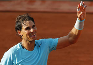 Photo - Spain's Rafael Nadal waves after defeating Robby Ginepri of the U.S. after their first round match of  the French Open tennis tournament at the Roland Garros stadium, in Paris, France, Monday, May 26, 2014. Nadal won 6-0, 6-3, 6-0.  (AP Photo/Michel Spingler)