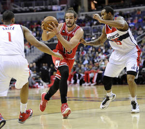 Photo - Chicago Bulls center Joakim Noah, center, drives to the basket against Washington Wizards' Trevor Ariza (1) and Trevor Booker (35) during the first half of an NBA basketball game, Saturday, April 5, 2014, in Washington. (AP Photo/Nick Wass)