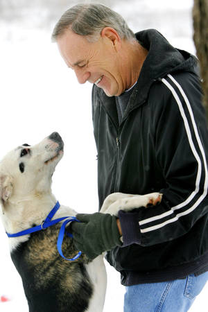 Photo - Ron Wingler, who died this month after spending 25 years as director of Free To Live no-kill animal shelter, plays with Dixie in 2008. OKLAHOMAN ARCHIVE photo