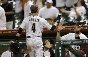Photo -   Houston Astros' Jed Lowrie (4) is congratulated after scoring a run during the eighth inning of a baseball game against the Philadelphia Phillies Thursday, Sept. 13, 2012, in Houston. (AP Photo/David J. Phillip)