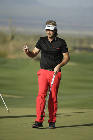 Photo - Victor Dubuisson, of France, waves on the eighth hole in his match against Ernie Els, of South Africa, during the fifth round of the Match Play Championship golf tournament on Sunday, Feb. 23, 2014, in Marana, Ariz. (AP Photo/Chris Carlson)