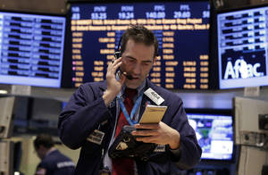 Photo - Trader Gregory Rowe works on the floor of the New York Stock Exchange Tuesday, Jan. 29, 2013. Stocks opened mixed on Wall Street, with the Standard & Poor's 500 holding at 1,500. (AP Photo/Richard Drew)