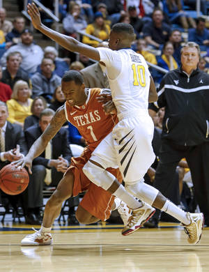 photo - Texas&#039; Sheldon McClellan (1) is fouled by West Virginia&#039;s Eron Harris (10) during the first half of an NCAA college basketball game at WVU Coliseum in Morgantown, W.Va., on Monday, Feb. 4, 2013. (AP Photo/David Smith)