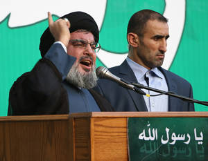 "photo -   Hezbollah leader Sheik Hassan Nasrallah, left, speaks to a crowd of tens of thousands of supporters, not shown, during a rally denouncing an anti-Islam film that has provoked a week of unrest in Muslim countries worldwide, in the southern suburb of Beirut, Lebanon, Monday Sept. 17, 2012. Nasrallah who does not usually appear in public for fear of assassination called for Monday's protests in Beirut, saying the U.S. must be held accountable for the film because it was produced in America. Arabic reads, ""the messenger of God."" (AP Photo/Hussein Malla)"