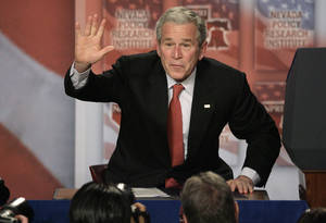 Photo - FILE - In this Jan. 31, 2008, file photo President Bush waves after signing a 15-day extension of the Protect America Act after a speech in Las Vegas. Sternly prodding Congress,  Bush told lawmakers they were jeopardizing the nation's safety by failing to lock in the government eavesdropping law. When the Protect America Act made warrantless wiretapping legal, lawyers and executives at major technology companies knew what was about to happen. They didn't know that its passage gave birth to a top-secret NSA program, officially labeled US-98XN. It was known as Prism. (AP Photo/Jae C. Hong, File)