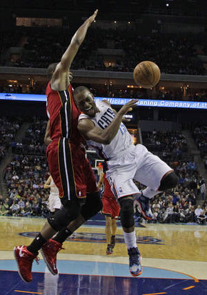 Photo - Charlotte Bobcats' Kemba Walker, right, loses the ball as he drives against Miami Heat's Chris Bosh, left, during the second half of an NBA basketball game in Charlotte, N.C., Saturday, Jan. 18, 2014. Walker was injured on the play. The Heat won 104-96 in overtime. (AP Photo/Chuck Burton)