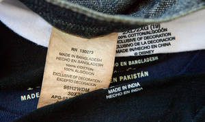 Photo - This photo illustration made Thursday, Dec. 13, 2012, shows labels of garments made in Bangladesh, India, China, and Pakistan, that were bought at a Wal-Mart store in Atlanta. Global clothing brands involved in Bangladesh's troubled garment industry responded in starkly different ways to the building collapse that killed more than 600 people. Some quickly acknowledged their links to the tragedy and promised compensation. Others denied they authorized work at factories in the building even when their labels were found in the rubble. (AP Photo/David Goldman)