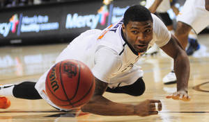 Photo - OSU guard Marcus Smart dives on the floor for a loose ball during Saturday's game against West Virginia. Smart finished with just four points in OSU's 81-75 win. Photo by KT King, The Oklahoman