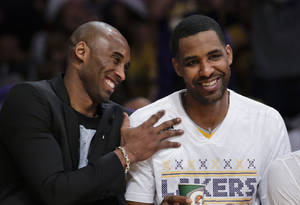 Photo - Los Angeles Lakers guard Kobe Bryant, left, sits on the bench with forward Shawne Williams during the first half of the Lakers' NBA basketball game against the Miami Heat in Los Angeles, Wednesday, Dec. 25, 2013. (AP Photo/Chris Carlson)