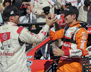 Photo - Kyle Larson, right, is congratulated by crew chief Scott Zipadelli, left, after winning the NASCAR Nationwide series History 300 auto race at Charlotte Motor Speedway in Concord, N.C., Saturday, May 24, 2014. (AP Photo/Chuck Burton)