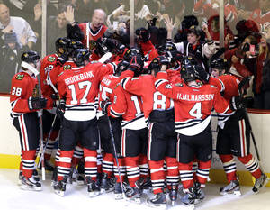 photo - Chicago Blackhawks' Brent Seabrook (7) celebrates with teammates after scoring his game-winning goal during the overtime of an NHL hockey game against the Columbus Blue Jackets in Chicago, Friday, March 1, 2013. The Blackhawks won 4-3. (AP Photo/Nam Y. Huh)