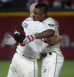 Photo - Atlanta Braves' B.J. Upton right celebrates his game-winning run with Brian McCann in the 11th inning against the Miami Marlins during a baseball game, Saturday, Aug. 31, 2013, in Atlanta. Atlanta won 5-4. (AP Photo/John Amis)