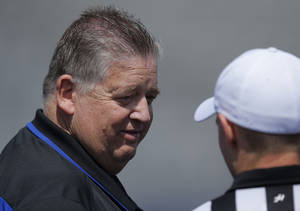 Photo - Kansas coach Charlie Weis talks with a referee before an NCAA college football spring game in Lawrence, Kan., Saturday, April 12, 2014. (AP Photo/Orlin Wagner)