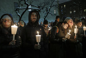 Photo - People listen to actor Eric Bogosian speak during a candlelight vigil for actor Philip Seymour Hoffman at the Bank Street Theater, home of the Labyrinth Theater Company, Wednesday, Feb. 5, 2014, in New York. Hoffman died Sunday of a suspected drug overdose. (AP Photo/Kathy Willens)