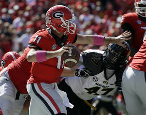Photo - Georgia quarterback Aaron Murray throws under pressure from Missouri's Kony Ealy during the second half of an NCAA college football game Saturday, Oct. 12, 2013, in Athens, Ga. Missouri won 41-26. (AP Photo/John Bazemore)