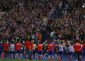 Photo - Atletico's players celebrate at the end of the Champions League quarterfinal second leg soccer match between Atletico Madrid and FC Barcelona at the Vicente Calderon stadium in Madrid, Spain, Wednesday, April 9, 2014. (AP Photo/Andres Kudacki)