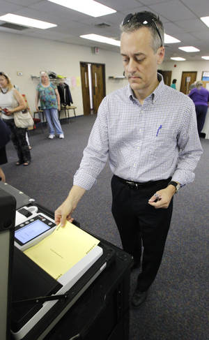 Photo - Wes Barnhill, of Oklahoma City, places his ballot into the voting machine Tuesday at precinct 012 in northwest Oklahoma City.  Photo by Paul B. Southerland, The Oklahoman <strong>PAUL B. SOUTHERLAND</strong>