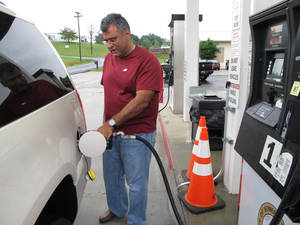 Photo - Samir Cook fills up his vehicle at a city-run station on Saturday, July 19, 2014, in Somerset, Ky. The station on the outskirts of Somerset opened to the public on Saturday, selling regular unleaded gas for $3.36 a gallon. In the first three hours, about 75 customers fueled up at the no-frills city station, where there are no snacks, no repairs and only regular unleaded gas. The city's mayor says he hopes the no-frills station will lower gas prices around town. (AP Photo/Bruce Schreiner)