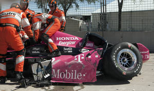 Photo - Safety team members work to remove Dario Franchitti, of Scotland, from his car after a crash during the second IndyCar Grand Prix of Houston auto race, Sunday, Oct. 6, 2013, in Houston. (AP Photo/Juan DeLeon)