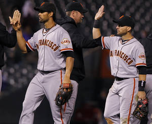 Photo -   San Francisco Giants shortstop Brandon Crawford, left, and second baseman Marco Scutaro are congratulated by teammates after the Giants' 8-3 victory in a baseball game in Denver on Wednesday, Sept. 12, 2012. (AP Photo/David Zalubowski)