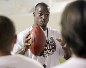 Photo - Adrian Peterson gives instructions during a football camp at OU's Everest Training Center in Norman, Okla., Friday, July 23, 2010. Peterson, an NFL running back and former player for the University of Oklahoma, gave the camp for at-risk youth from the Seeworth Academy. Photo by Nate Billings, The Oklahoman ORG XMIT: KOD