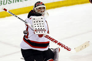 photo - New Jersey Devils goalie Martin Brodeur deflects a shot during a scrimmage against the Albany Devils, the team's AHL farm team, Wednesday, Jan. 16, 2013, in Newark, N.J. (AP Photo/Julio Cortez)